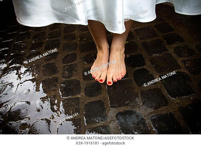 Bride's bare feet on wet san pietrini stones in Rome Italy