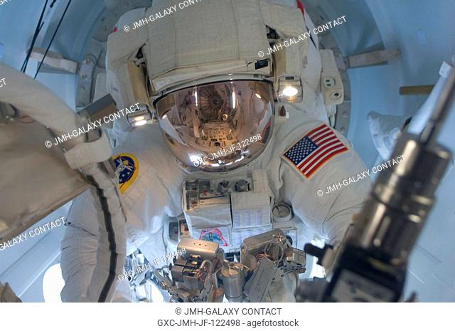 Astronaut Joseph Acaba, STS-119 mission specialist, attired in his Extravehicular Mobility Unit (EMU) spacesuit, enters the Quest Airlock of the International...