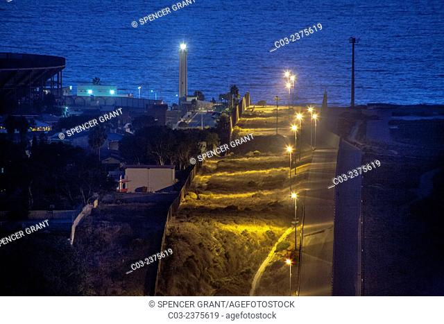 Sodium vapor lights illuminate the hilly international border between the U.S. and Tijuana, Mexico at left. Note Pacific Ocean and lighthouse in background
