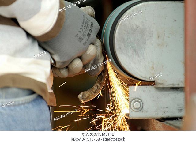 Farrier at work, grinding horseshoe