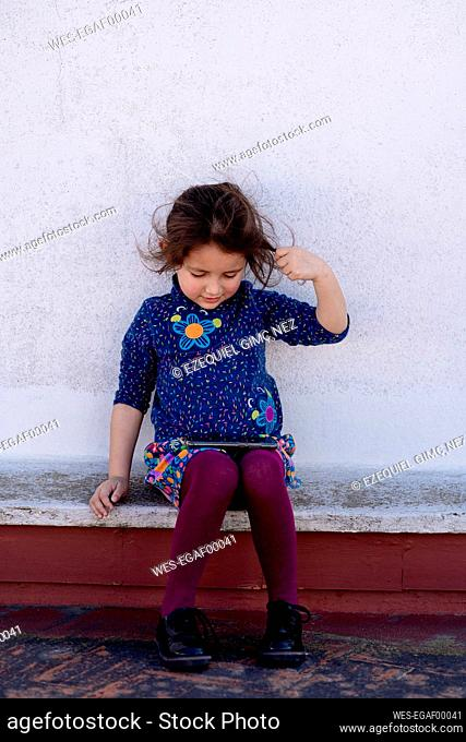 Little girl sitting on rooftop looking at cell phone