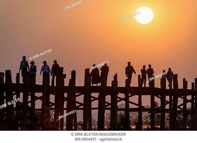 Locals, monks and tourists walking on a teak bridge, U Bein Bridge across Thaungthaman Lake at sunset, Amarapura, Mandalay Division, Myanmar