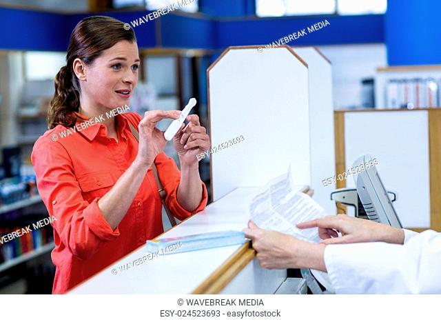 Pharmacist assisting medicine to customer