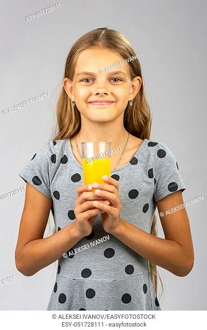 A girl holds a glass of juice in her hands with both hands