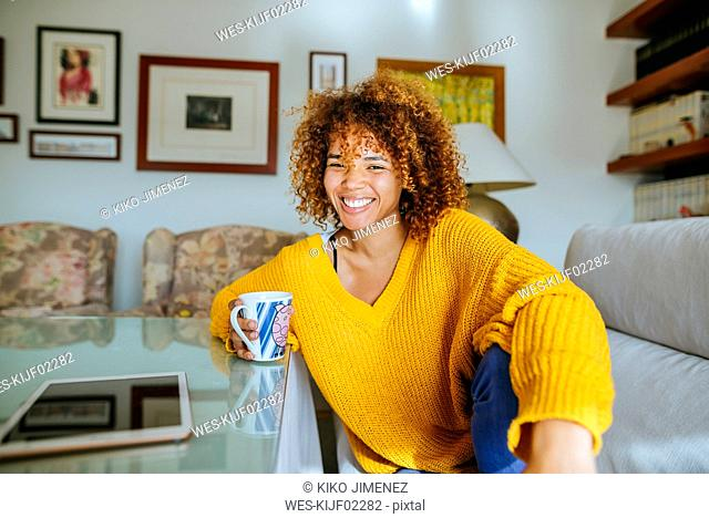 Portrait of happy young woman with curly hair holding mug at home