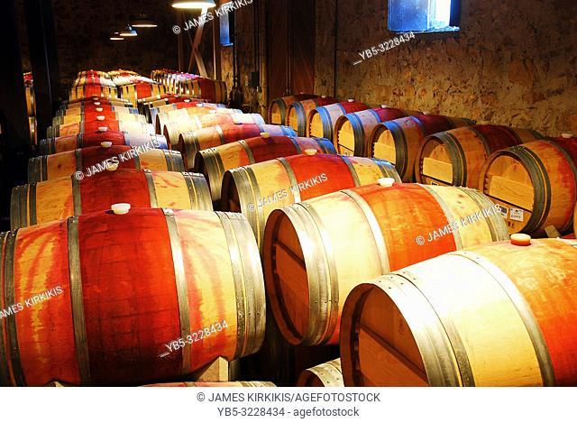Barrels of wine age in a basement