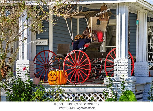 Carved Halloween jack-0-lantern pumpkin and headless horseman in a buggy on wooden porch of house in Green Cove Springs, Florida