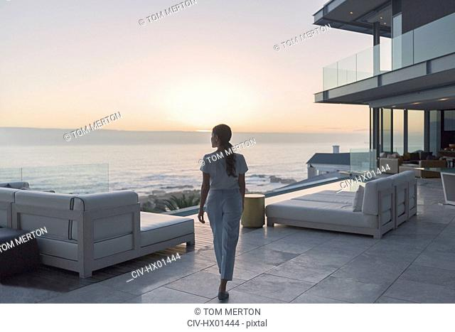 Woman walking on luxury home showcase exterior patio at sunset