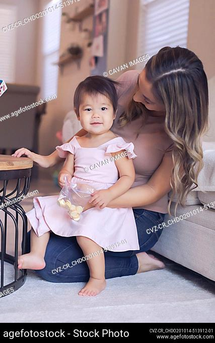 Baby girl's snack time with mom in the living room