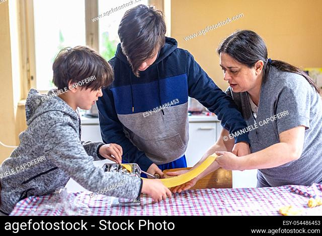 mother with children prepares homemade tagliatelle pasta