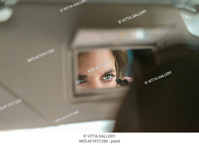 Woman mirrored in rear view mirror applying mascara in car