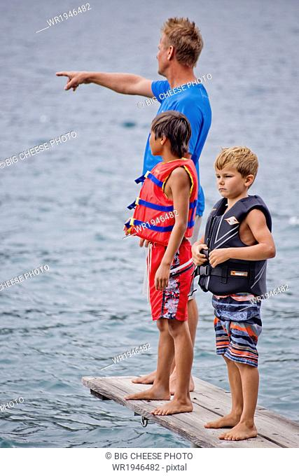 Man and two boys standing on a dock in a lake
