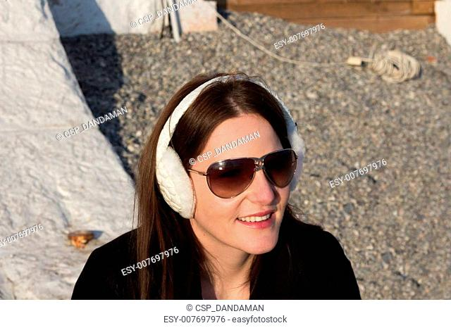 Woman With White Ear Muffs And Sunglasses