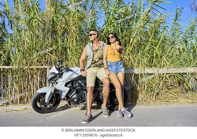 couple leaning against motorcycle during day trip. Greek ethnicity. In holiday destination Hersonissos, Crete, Greece