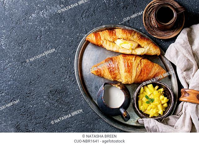Breakfast with two croissant, butter, cup of coffee, cream and sliced mango fruit, served on serving metal tray with textile napkin over black concrete texture...