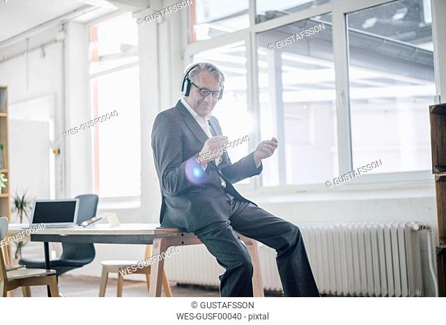 Happy senior businessman listening to music with headphones in office