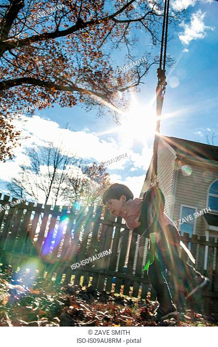 Low angle side view of boy playing on swing in garden
