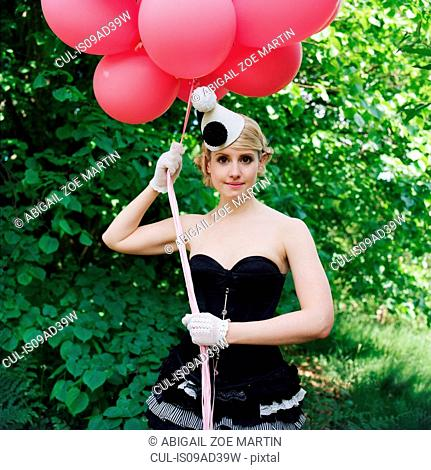 Woman wearing basque holding red balloons