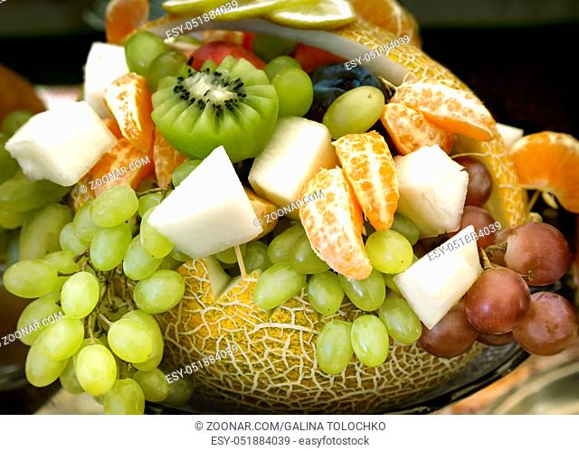 Big pumpkin, decorated in the form of a basket and filled with a variety of fruit: grapes, kiwi, bananas, tangerines
