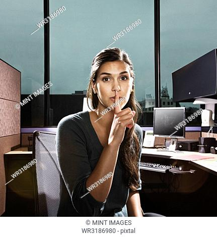 Hispanic woman asking for quiet in an office cubicle