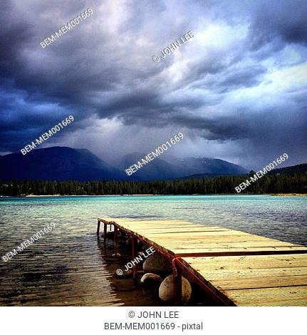 Wooden dock over remote lake near mountain