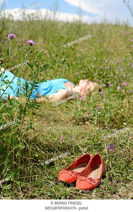 Young woman lying in wildflower meadow