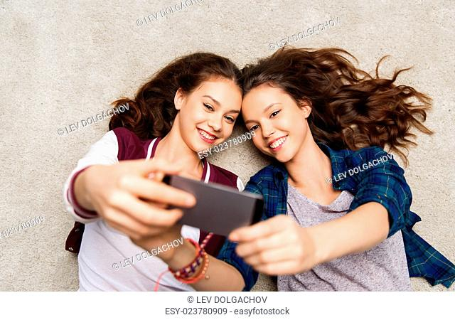 people, friends, teens and friendship concept - happy smiling pretty teenage girls lying on floor and taking selfie with smartphone