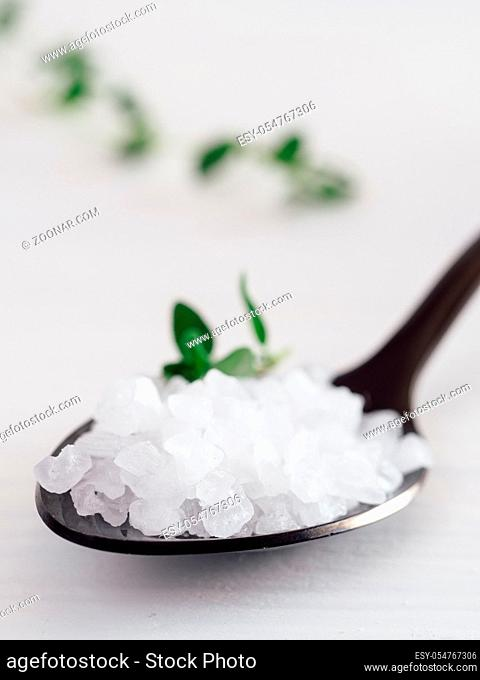 coarse sea salt in black spoon on white background with thyme. Copy space