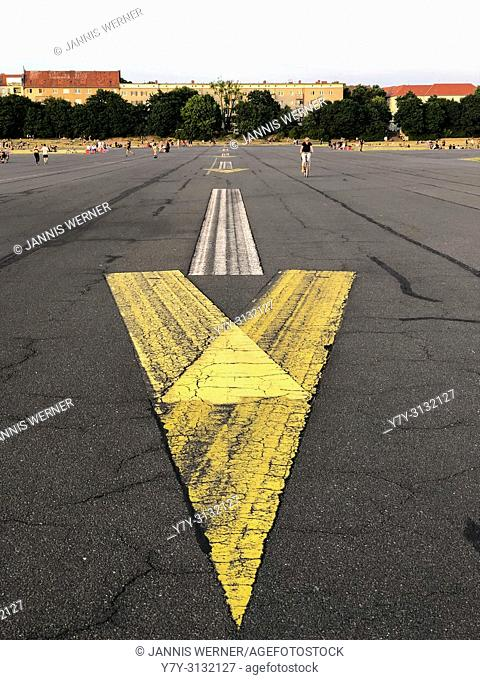 Painted arrow sign on the asphalt of the old runway at Tempelhofer Feld in Berlin, Germany in summer 2018