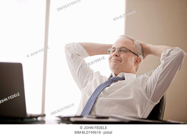 Caucasian businessman sitting at desk with hands on head