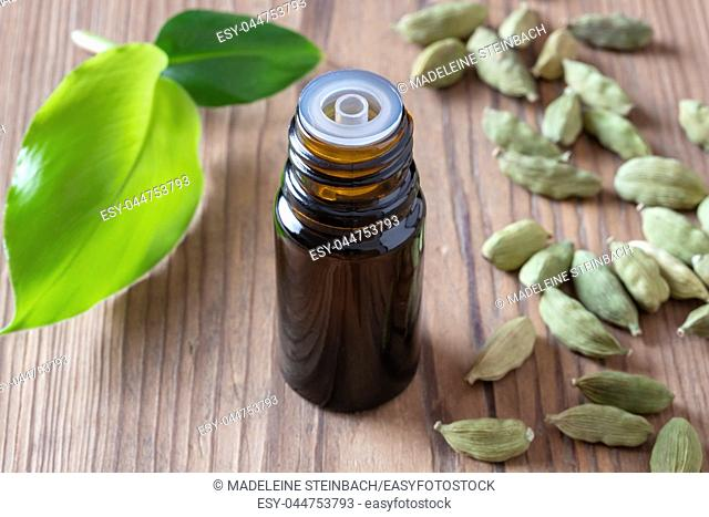 A bottle of essential oil with cardamon pods and leaves