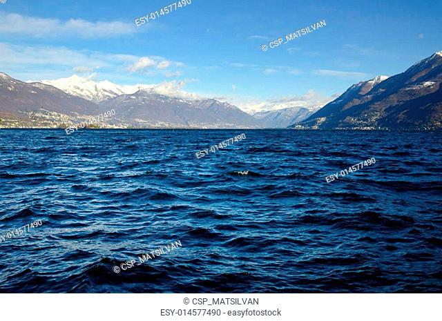 Lake with snow-capped mountains and blue sky and clouds