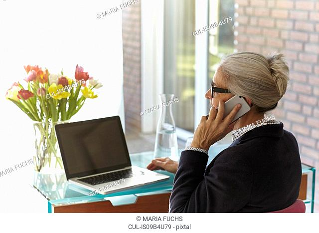 Senior businesswoman using laptop and making smartphone call at home desk