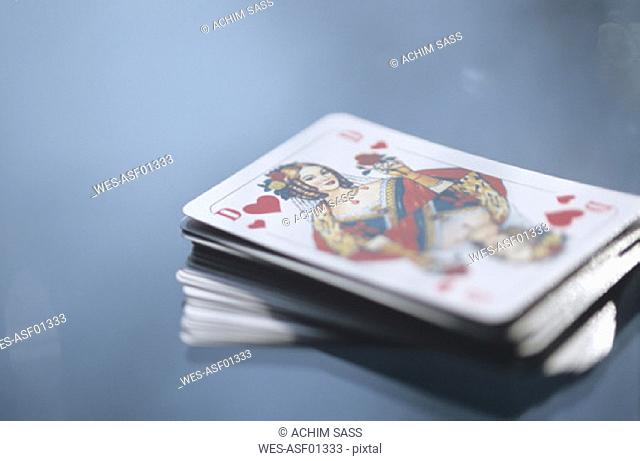 Pack of cards on a table, queen of hearts