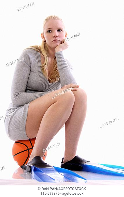 Young girl with acnes sitting on a basketball and wearing swimming flippers looking depressed