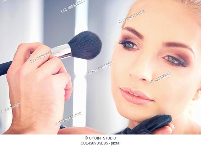 Hand of make up artist applying blusher to model for photo shoot