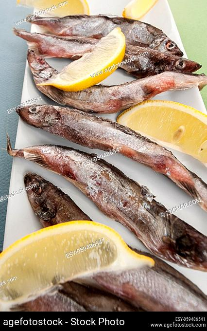 Composition with freshly frozen capelin and lemon close-up on a blue-green background