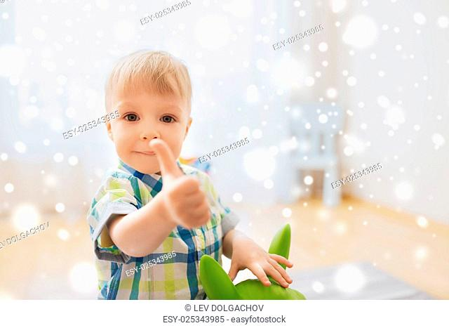 childhood, toys and people concept - happy little baby boy playing with ride-on toy horse and showing thumbs up at home over snow