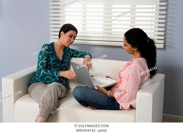 Two women with laptop talking in the living room