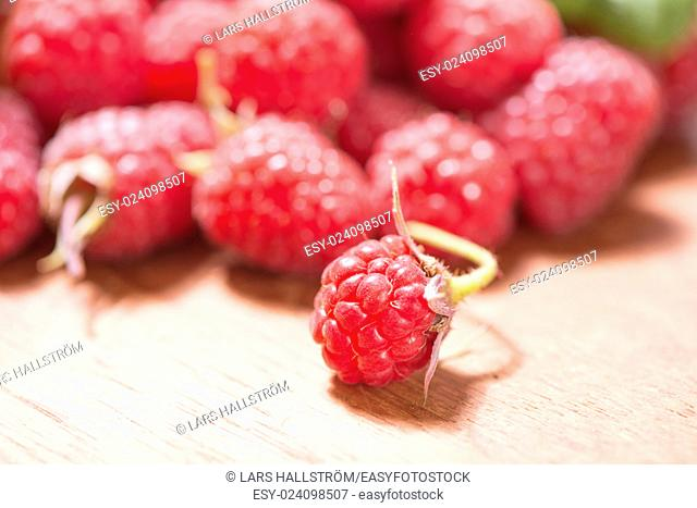 Raspberries in close-up. They are fresh, ripe and red. Tasty food image with juicy berries