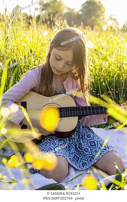 Portrait of little girl playing guitar on field of flowers