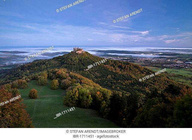 Burg Hohenzollern Castle in the morning light with autumn forests, early morning fog, Swabian Alb, Baden-Wuerttemberg, Germany, Europe