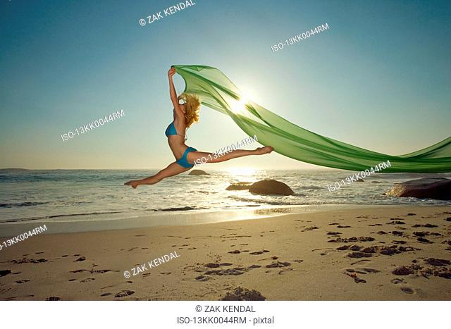 Dancer leaping on a beach