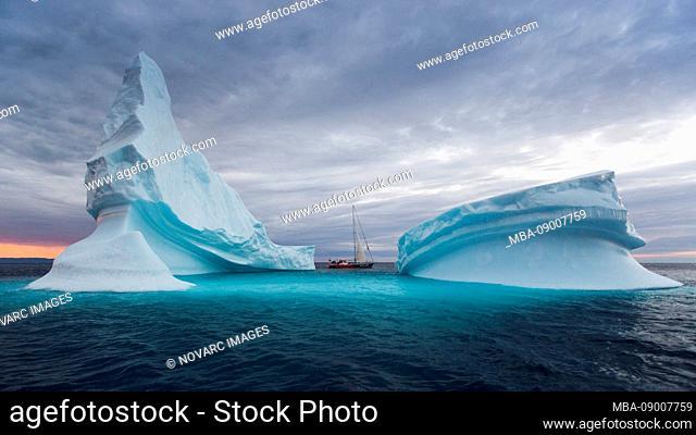 Icebergs and sailboat in Disko Bay on Midsummer, Greenland