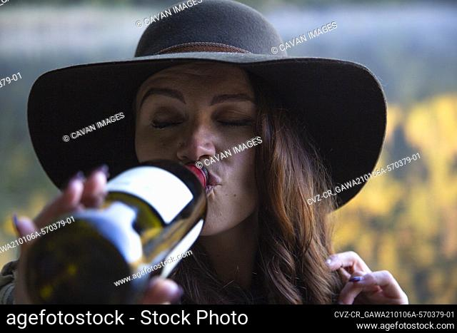 A hipster girl takes a swig of red wine from the bottle