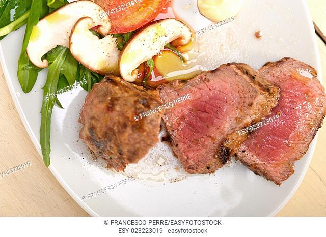 beef filet mignon grilled with fresh vegetables on side , mushrooms tomato and arugula salad