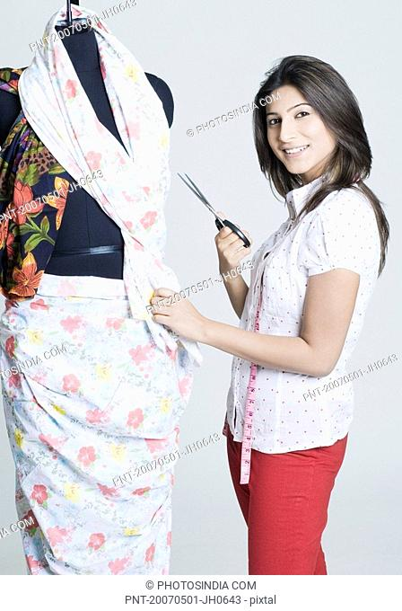 Portrait of a young woman holding a pair of scissors near a mannequin and smiling