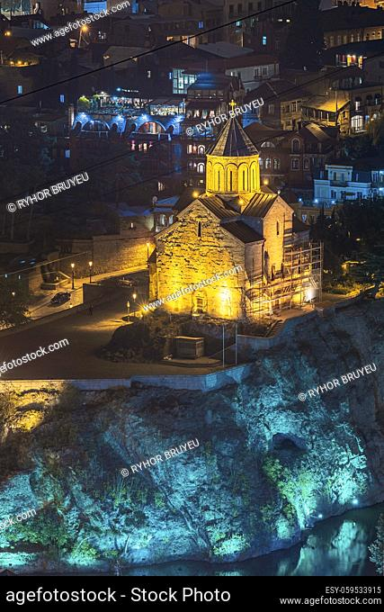 Tbilisi, Georgia. Night Evening Illuminated View Of Metekhi Church And Equestrian Statue Of King Vakhtang Gorgasali On Metekhi Cliff In Old Historic District...