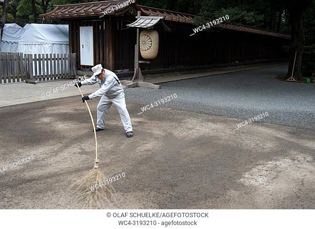 Tokyo, Japan, Asia - A temple worker is sweeping the grounds of the Meiji Shrine in Shibuya with a besom