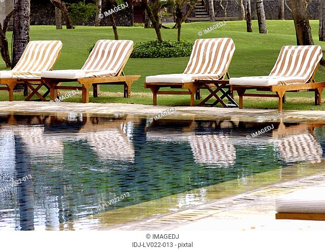 View of deck chairs by a swimming pool